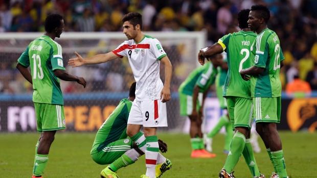 Alireza Jahanbakhsh de l'Iran, tend la main à Juwon Oshaniwa du Nigeria après le match de football Coupe du monde de F de groupe entre l'Iran et le Nigeria à l'Arena da Baixada à Curitiba, au Brésil, le lundi 16 Juin 2014. Le match s'est terminé sur un 0 -0 . (AP / Fernando Vergara)